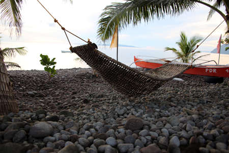 Hammock on pebble beach, Pintuyan, Panaon Island, Southern Leyte, Philippines