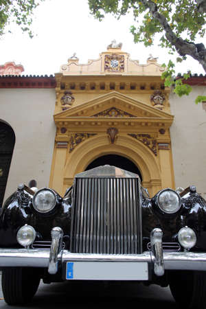 luxury vintage car as a wedding car in front of St Mary Magdalene, Seville, Andalusia, Spain