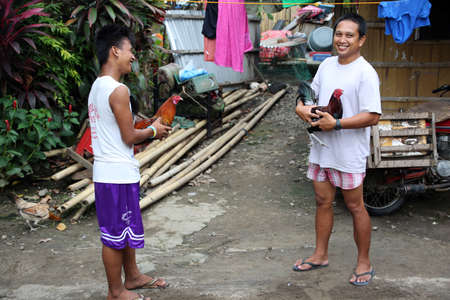 Two young men present their fighting roaches, Pintuyan, Panaon Island, Southern Leyte, Philippines