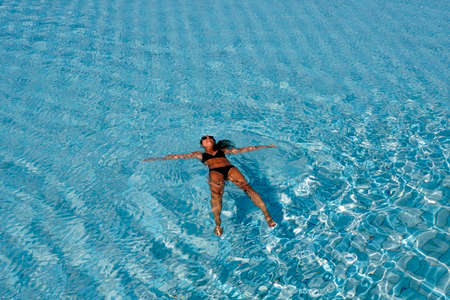 Young woman in bikini floats on the water, El Quseir, Egypt