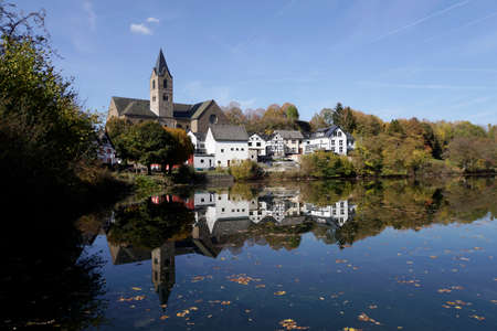 Parish church of St. Matthias is reflected in the maar at the Eifel town of Ulmen, Rhineland-Palatinate, Germany Stock Photo - 110762472