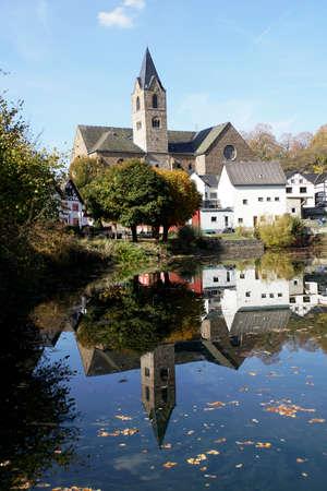 Parish church of St. Matthias is reflected in the maar in the Eifel town of Ulmen, Rhineland-Palatinate, Germany
