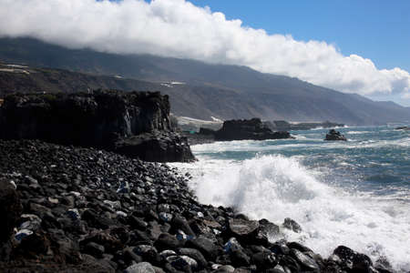 Surf on the lava coast at La Bombadilla, in the background Passat cloud over the Cumbre Vieja, Los Llanos de Aridane, La Palma, Canary Islands, Spain