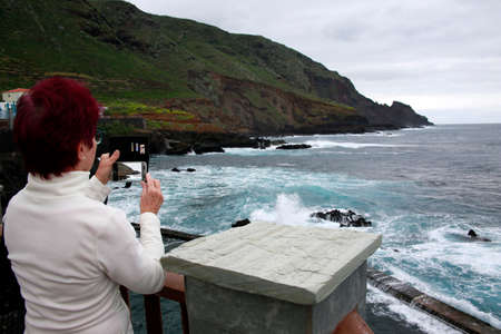 Woman is photographing with her smart phone branding at the rocky coast at La Fajana, La Palma, Canary Islands, Spain