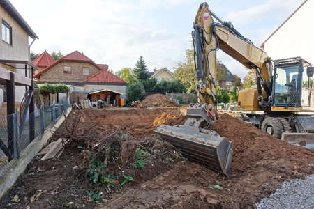Excavator in front of an excavation pit to build a house Stockfoto