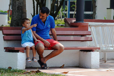 Parenting at parkbench - father and son sitting on wooden bench while cute toddler is pointing at something