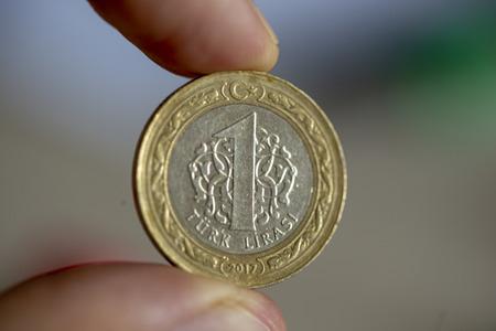 1 Turkish lira coin 2017 obverse on blurred background. Finger tips.