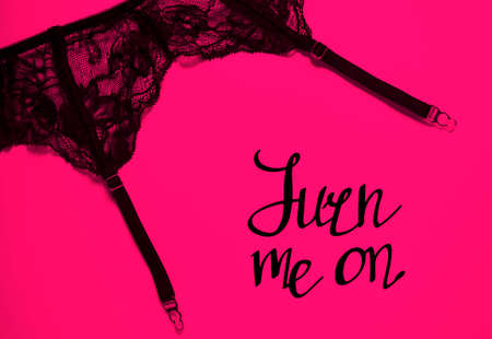 Garter belt on pink background. Turn me on, handwritten lettering. Sexual female lingerie. Erotic underwear, black delicate girdle. Passion and romantic theme. Happy Valentine's Day!
