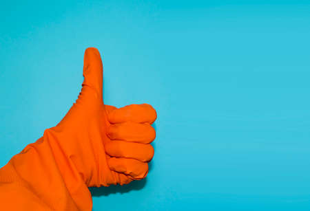 Thumbs-up sign on blue background. Usage of protective glove to prevent infection. Hand gesture of agreement and positive answer.