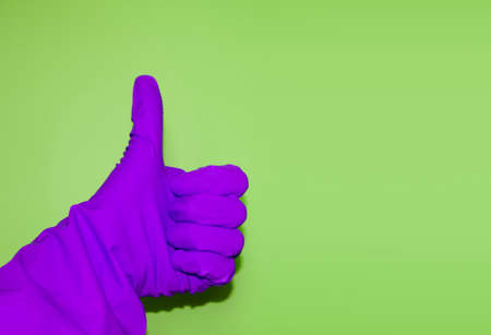 Thumbs-up sign isolated on green background. Usage of protective glove to prevent infection. Hand gesture of agreement and positive answer. Banque d'images