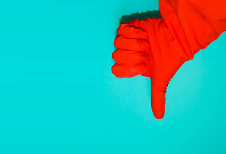 Hand gesture of dislike and negative answer. Thumbs-down gesture indicating disapproval. Banner with hand in protective glove and copy space. Banque d'images