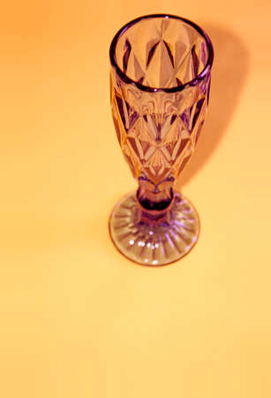 Wineglass on yellow background with copy space. Composition of crystal glasswear.