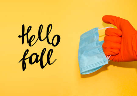 Hand in protective glove holds face mask. Hello fall. Banner template with stuff for health care and infection prevention.
