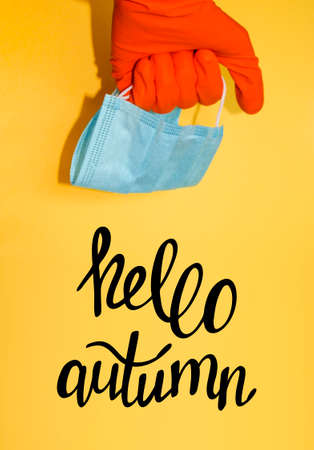 Hand in protective glove holds face mask. Hello autumn. Global quarantine during fall season. Banner template with stuff for health care and infection prevention.