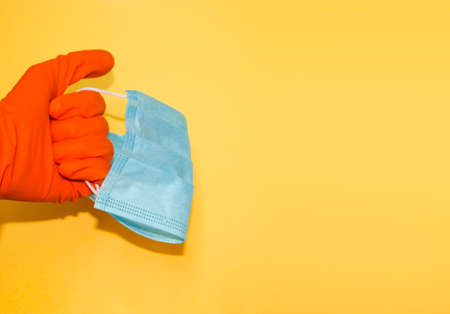 Hand in protective glove holds face mask. Stuff for health care and infection prevention. Banner template with copy space.