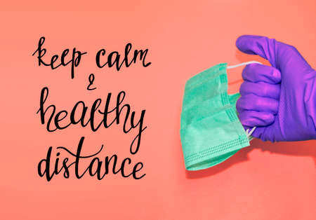 Keep calm and healthy distance. Hand in protective glove holds face mask. Banner with stuff for health care and infection prevention. Banque d'images