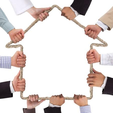 investment solutions: Manos que sostienen la cuerda formando casa