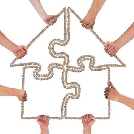 investment solutions: Hands holding puzzle forming house