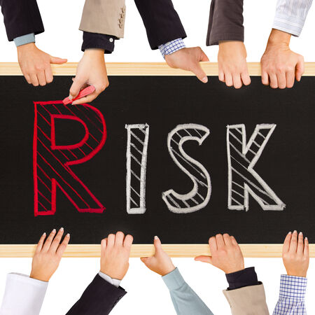 risky innovation: Photo of business hands holding blackboard and writing RISK concept