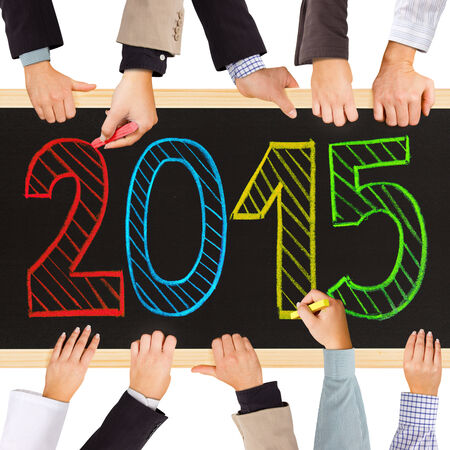 Photo of business hands holding bricks forming year 2015 photo