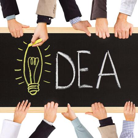 sinergia: Foto de las manos de negocios la celebración de pizarra y escribir concepto IDEA