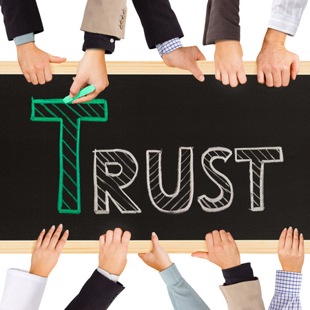 business hands holding blackboard and writing TRUST concept photo