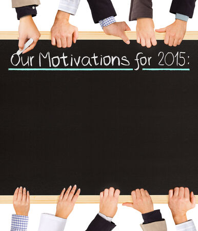 motivations: Photo of business hands holding blackboard and writing Our Motivations for 2015 Stock Photo