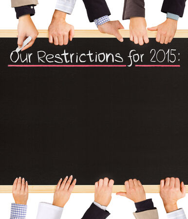 restrictions: Photo of business hands holding blackboard and writing Our Restrictions for 2015