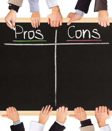 cons: Photo of business hands holding blackboard and writing Pros and Cons