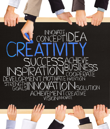 innovation word: Photo of business hands holding blackboard and writing CREATIVITY Stock Photo