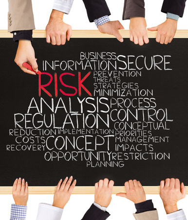risky innovation: Photo of business hands holding blackboard and writing RISK