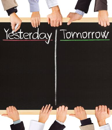 yesterday: Photo of business hands holding blackboard and writing Yesterday and Tomorrow
