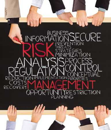 risky innovation: Photo of business hands holding blackboard and writing RISK MANAGEMENT