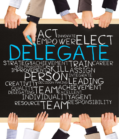 delegate: Photo of business hands holding blackboard and writing DELEGATE word cloud Stock Photo