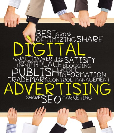 adwords: Photo of business hands holding blackboard and writing DIGITAL advertising word cloud
