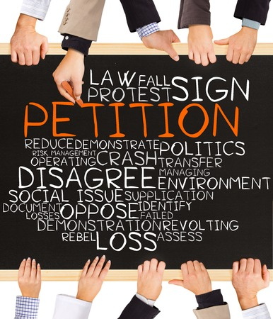 social issue: Photo of business hands holding blackboard and writing PETITION concept Stock Photo