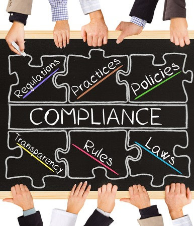 Photo of business hands holding blackboard and writing COMPLIANCE diagram Stock Photo