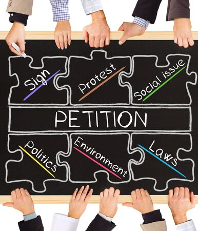 petition: Photo of business hands holding blackboard and writing PETITION concept Stock Photo