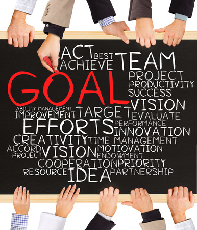 Photo of business hands holding blackboard and writing GOAL word cloud
