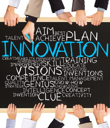 innovation word: Photo of business hands holding blackboard and writing INNOVATION word cloud