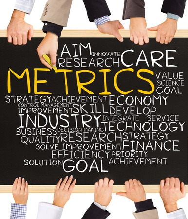 metrics: Photo of business hands holding blackboard and writing METRICS word cloud
