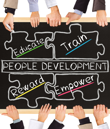 attribute: Photo of business hands holding blackboard and writing PEOPLE DEVELOPMENT diagram