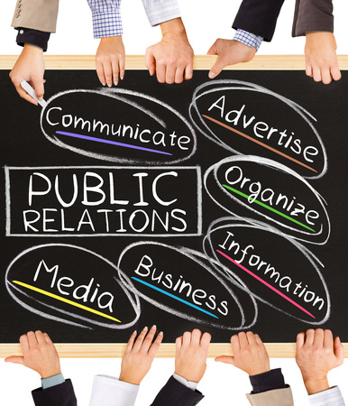 news values: Photo of business hands holding blackboard and writing PUBLIC RELATIONS diagram