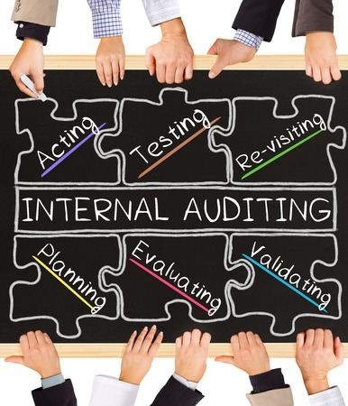 auditing: Photo of business hands holding blackboard and writing INTERNAL AUDITING diagram Stock Photo