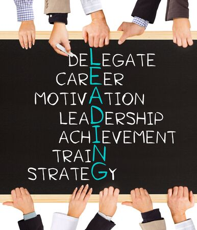 role models: Photo of business hands holding blackboard and writing LEADING concept