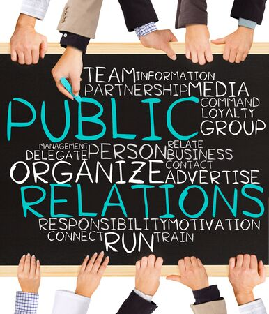 news values: Photo of business hands holding blackboard and writing PUBLIC RELATIONS word cloud Stock Photo