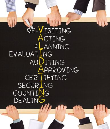 validating: Photo of business hands holding blackboard and writing VALIDATION concept Stock Photo