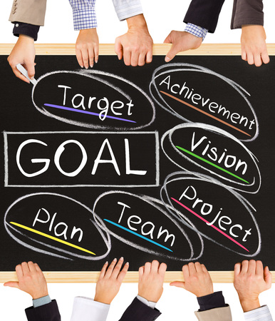 Photo of business hands holding blackboard and writing GOAL diagram