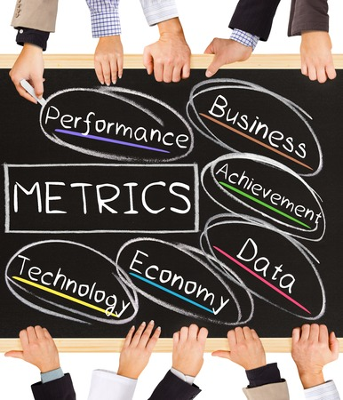 metrics: Photo of business hands holding blackboard and writing METRICS diagram