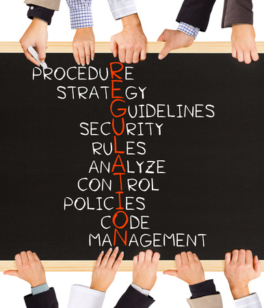 regulations: Photo of business hands holding blackboard and writing REGULATION concept Stock Photo
